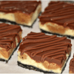 PEANUT BUTTER COOKIE DOUGH CHEESECAKE BARS ON AN OREO CRUST AND TOPPED WITH A MILK CHOCOLATE GLAZE!