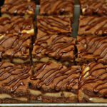 CHOCOLATE COOKIE BARS STUFFED WITH PEANUT BUTTER CUP CHEESECAKE